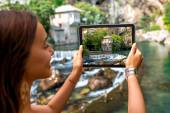 Woman photographing house on Buna spring in Blagaj village — Stock Photo