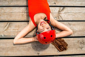 Woman in sportswear resting on the wooden boards — Stock Photo