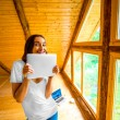 Woman with digital tablet in wooden house — Stock Photo #77408872