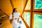 Woman with digital tablet in wooden house — Stock Photo