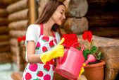 Woman watering flowers near the wooden cottage — ストック写真