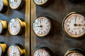 Metal wall with old styled clocks — Stock Photo