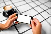 Utilizzando il telefono cellulare con caffè su priorità bassa — Foto Stock
