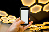 Holding phone on the modern light background — Stock Photo