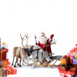 Santa Claus with his reindeer and gifts — Stock Photo #52761777
