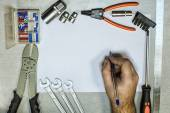 Tools and hand with a ballpoint pen — Stockfoto