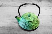 Green teapot on grey wooden background — Stock Photo