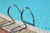 Grab bars ladder in the blue swimming pool — Photo