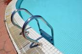 Grab bars ladder in the blue swimming pool — Stock Photo