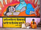 Indian Man Sitting By Colorful Hindu Art in Varanasi, India — Stock Photo