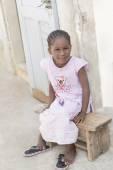 Afro girl sitting on a bench, 6 years old — Stock Photo