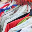 Shop shirts colorful fabric hanging on a rack. — Stock Photo #51942941