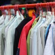 Shop shirts colorful fabric hanging on a rack. — Stock Photo #52366397