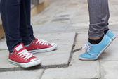 Men and women legs wearing sneakers. — Stock Photo