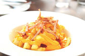 French fries topped with cheese on plate. — Stock Photo