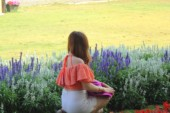 Blurred woman in a flower garden — Stock Photo