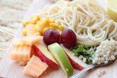 Pasta spaghetti with salad mix fruit. — Stock Photo