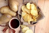 Potato chip and fresh potatoes on wood background — Foto Stock