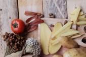 Potato chip and fresh potatoes on wood background — Stock Photo