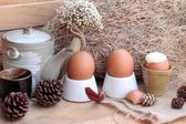 Soft-boiled egg and eggs on wood background — Stock Photo