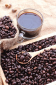Roasted coffee beans with hot coffee — Stock Photo