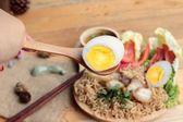 Soupe de nouilles instantanées, mettre les oeufs et le porc croustillant — Photo