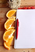Diary book with orange and tomatoes slice on wooden background. — Stock Photo