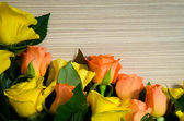 Yellow and orange roses on wooden background — Stock Photo