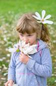 Beautiful blond girl smelling flowers — Stock Photo