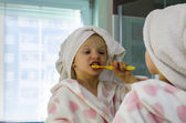 Portrait of girl in dressing-gown with towel over head — Stock Photo
