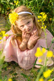 Adorable girl in yellow flowers — Stock Photo