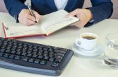 Hand with pen, notepad, coffee, glass of water and keyboard — Stockfoto