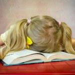 Girl sleeping over open book — Stock Photo #75961629