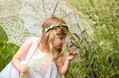 Girl with sunshade umbrella smelling flower — Stock Photo