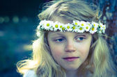 Smiling blond girl with big blue eyes and with daisies on head — Stock Photo