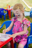 Girl with face-painting drawing — Stock Photo