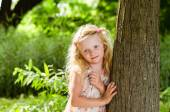 Smiling blond girl leaned to the tree — Stock Photo