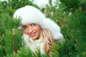Woman in a hat, mittens, scarves, sweaters, fur in winter fir forest — Stockfoto