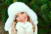 Woman in a hat, mittens, scarves, sweaters, fur in winter fir forest — Stock Photo