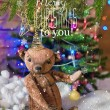 Christmas card with teddy bear, Christmas tree, ornaments, gold glitter, fir branches and greeting text. — Stock Photo #59692693