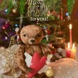 Christmas card with teddy bear, Christmas tree, ornaments, gold glitter, fir branches and greeting text. — Stock Photo #59692877