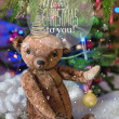 Christmas card with teddy bear, Christmas tree, ornaments, gold glitter, fir branches and greeting text. — Stock Photo #59693707