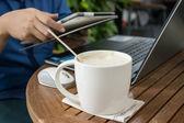 Uomo con una tazza di caffè, lavorando sul suo portatile — Foto Stock