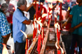 Hand cense joss stick to at an incense burne and burning candle — Stock Photo