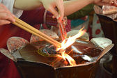 Hand cense joss stick to at an incense burne — Stock Photo