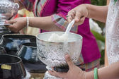 Puts food offerings in a Buddhist monk's alms bowl — Stockfoto