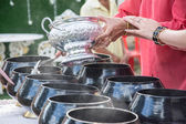 Puts food offerings in a Buddhist monk's alms bowl — Stock Photo