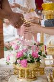 Hand of a bride receiving holy water from elders in thai culture wedding ceremony — Stock Photo