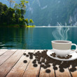 Cup with coffee on table over lake — Stock Photo #77367542