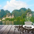 Cup with coffee on table over lake — Stock Photo #77368726